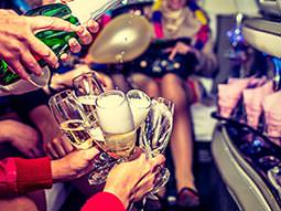 Close up of a hand pouring a bottle of champagne into several glasses as a woman holds them