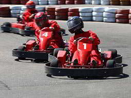 Three red karts driving on an outdoor track