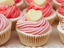 Close up of two rows of pink cupcakes with love hearts on top