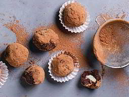 Chocolate truffles dusted with cocoa powder and a sieve