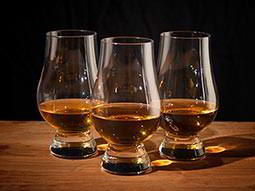 Three brandy glasses with brandy in, on top of a wooden table