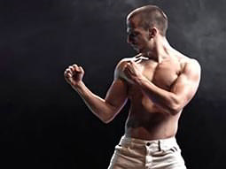 A man in white pants, holding his arms up as if he were about to fight