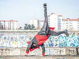 A man doing a handstand in front of a graffiti wall, with buildings in the far distance