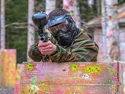 A man aiming with a paintball gun whilst stood behind a fence