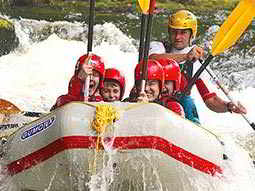 A group of people battling the rapids in a white water raft