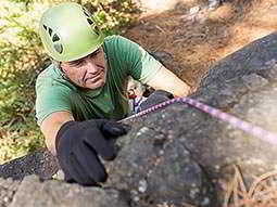 Image of a man taken from above, wearing a hard hat and black gloves, climbing a steep wall