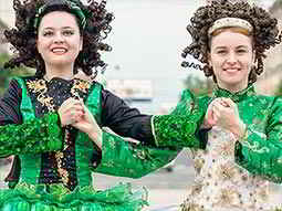Two women in traditional Irish costumes holding hands