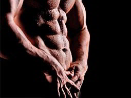 A naked male torso to a black backdrop