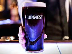A hand holding a pint of Guinness