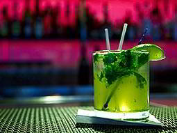 A green cocktail with mint and lime on a bar top