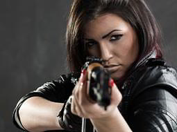 A woman aiming with a gun towards the camera