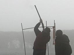The back of a man aiming a shotgun to the sky with a man looking on, to a foggy backdrop