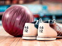 A pair of bowling shoes next to a red bowling ball, with the bowling alley in the background