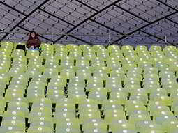 One person sitting in the seats in Munichs Olympic Stadium