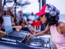 Tables and chairs under wicker parasols, outside a bar