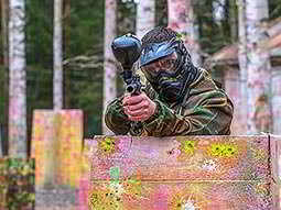 A man holding a paintball gun whilst shielding the bottom half of his body behind a fence