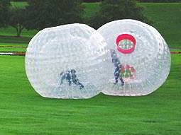 Two large inflatable zorbs on green grass, with people inside
