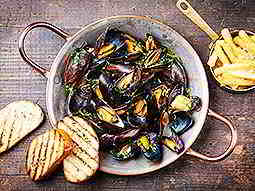 Some mussels in a bowl with bread and chips to the side