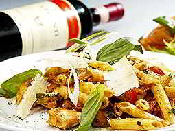 A pasta meal with salad leaves on top, and a bottle of red wine lying in the background
