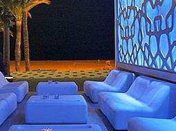 Some plush, white seats in Moon Beach club, with palm trees in the background