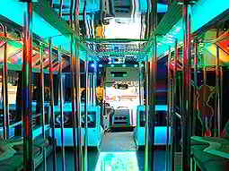 Interior of a party bus with seating on the sides and poles in the middle