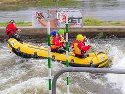Four people in a raft on an outdoor white water rafting course