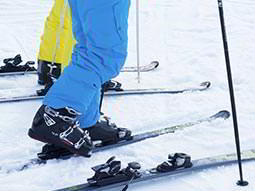 Two people wearing yellow and blue ski suits, whilst on the slops