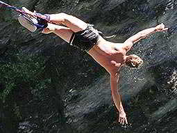 A man in shorts, with no top, bungee jumping to a backdrop of a cliff