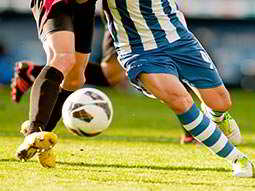 two pairs of footballers legs on the pitch playing football