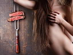 A woman cupping her breast, next to a skewer with steak on