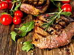 Two large steaks with tomatoes on the side, on a wooden board
