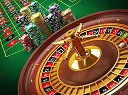 A roulette wheel, with poker chips stacked up and a roulette table in the background