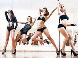 Four women dancing on poles in their black underwear