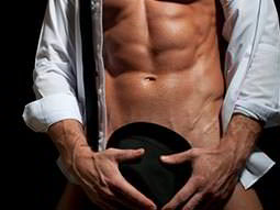 A naked man in a white shirt, holding a black hat over his genitals