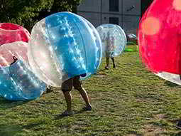 Some people in inflated zorbs, playing bubble football outdoors