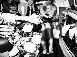A black and white image of cluster of champagne glasses being filled inside a large vehicle