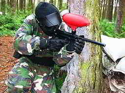 A person wearing camouflage overalls and a mask aiming a paintball marker from behind a tree