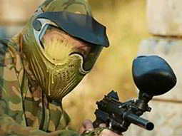 A person wearing camouflage pointing a paintball gun at the camera, with paint on their visor