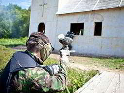 The back of a man in camouflage and holding a paintball gun as he points it at a white church on a paintball field