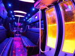 The blue and purple interior of a party bus, with a door in the corner