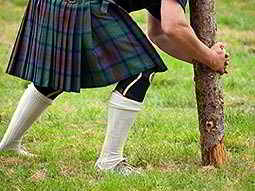 Close up of a man in a kilt and white socks, attempting to pick up a log