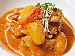 A bright orange Thai curry on a white plate