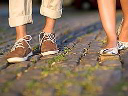 A man and woman's legs walking along a cobbled street