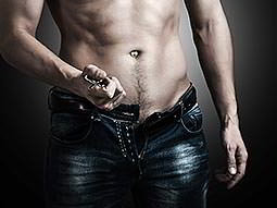 A semi-naked man pulling the belt off of his jeans