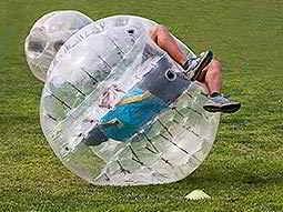 A man upside down in an inflatable zorb on grass
