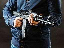 A black Kalashnikov-style rifle being aimed away