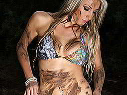 A woman in a bikini, covered with streaks of mud