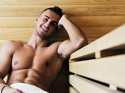 A man relaxing in a sauna with just a white towel on