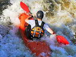 A man in an orange kayak paddles through turbulent rapids