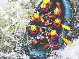 A birds eye view of some people on a raft battling white water rapids